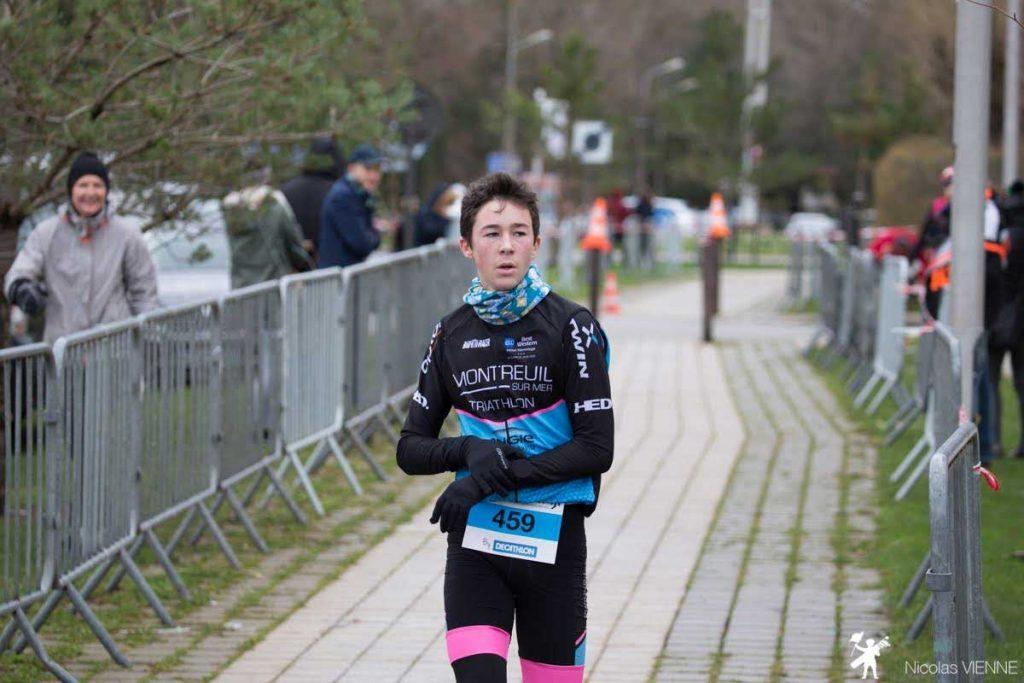 jeune adolescent sur la ligne d'arrivée de la course trail des 2 baies Ado.